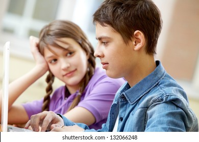 Close-up image of a school girl sitting by her computing friend