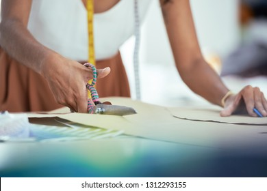 Close-up image of seamstress cutting paper pattern for the shirt or blouse