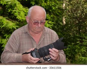 closeup image of senior adjusting a zoom lens onto dslr
