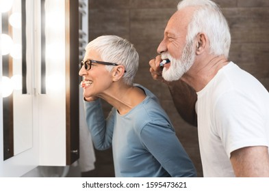 Closeup image of senior couple brushing their teeth together in the bathroom