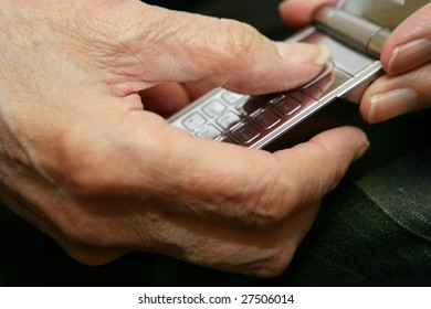 Close-up image of the senior man hands using a mobile phone.