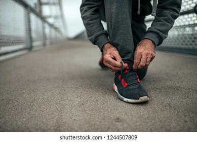 Close-up image of senior runner tying shoelaces.
