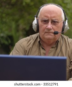 Close-up image of a senior using a laptop and voice call