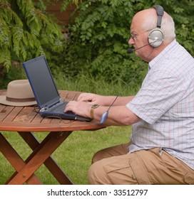 Close-up image of a senior using a laptop outside. headphones voip online internet oap