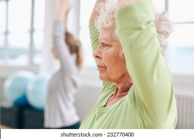 Close-up image of senior woman practicing yoga at gym. Active senior woman exercising at health club with female trainer in background.