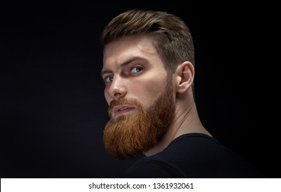 Close-up image of serious brutal bearded man on dark background Confident and dramatic concept