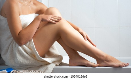 Closeup image of sexy young woman in bath towel sitting at bathroom