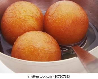 """A closeup image showing Indian sweet dish called """" gulab jamun """"."""