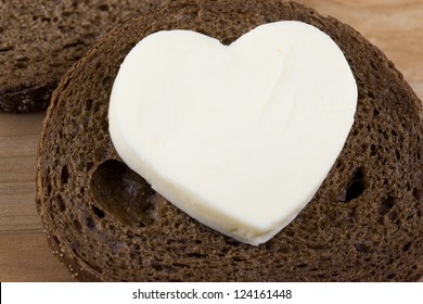 Close-up image of a slice of bread with heart shaped butter