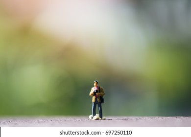 Closeup image of a small photographer model figure standing on wooden floor with blur green nature background