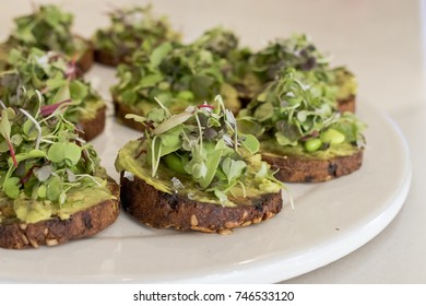 Closeup image of small toasts with avocado and lettuce.