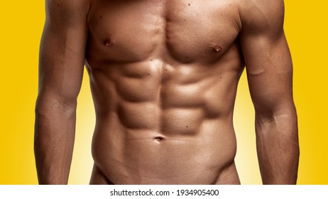 Closeup image of a strong athletic man showing muscular body and sixpack abs isolated yellow background.