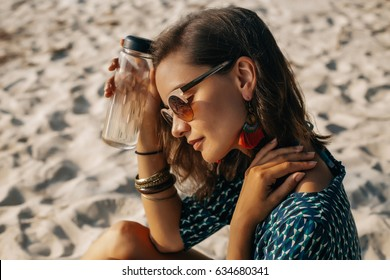 close-up image of style young woman relaxing on the beach,boho chic,style and beauty,fashionable girl,accessory store,trendy, sunglasses, A bottle of water in hand, hot weather, thirst