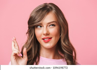 Closeup image of superstitious brunette woman in basic clothing holding fingers crossed and hoping for good luck isolated over pink background
