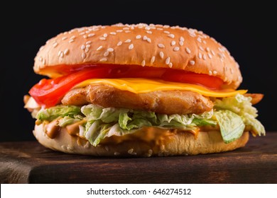 Closeup image of tasty cheeseburger on wooden board at dark background.
