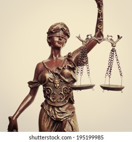 closeup image of Themis goddess or lady justice holding scale blindfold on light background