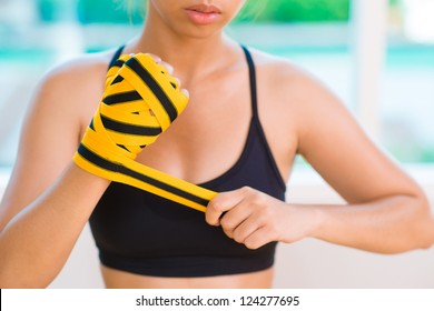 Close-up image of a tough girl taping her hand