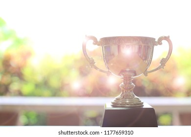 Close-up image of a trophy on the floor flare of colorful sunshine as background selective focus and shallow depth of field