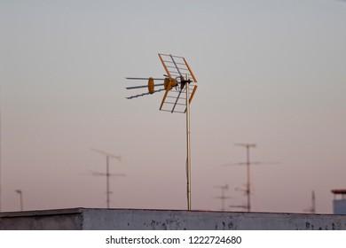 Closeup image of a TV antenna at dusk.