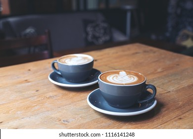 Closeup image of two blue cups of hot latte coffee with latte art on vintage wooden table in cafe