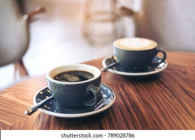 Closeup image of two blue cups of hot latte coffee and Americano coffee on vintage wooden table in cafe