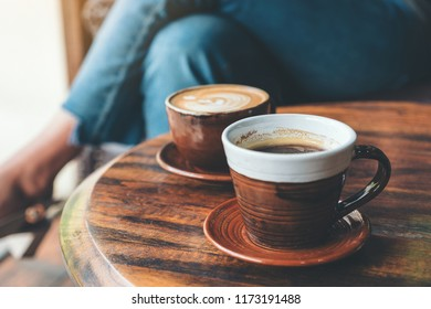 Closeup image of two cups of hot latte coffee and black coffee on vintage wooden table in cafe
