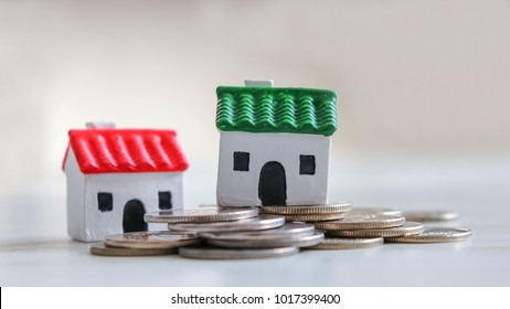 Close-up image of two miniature house and coins.
