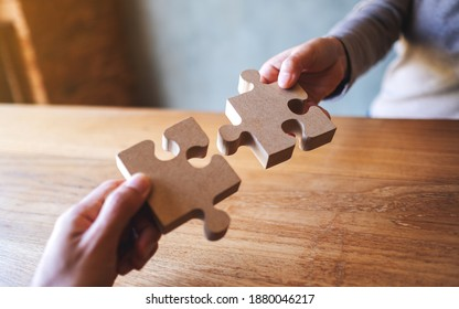 Closeup image of two people holding and putting a piece of wooden jigsaw puzzle together