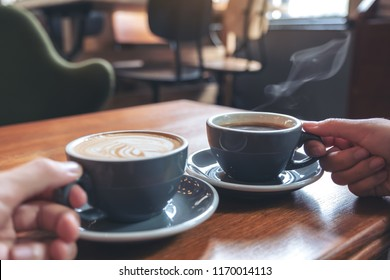 Closeup image of two people's hands holding coffee and hot chocolate cups on wooden table in cafe