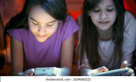 Closeup image of two teenage girls lying on floor and using mobile phones at night