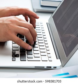 Close-up image of typing male hands at laptpp
