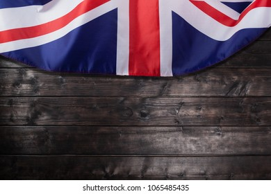 Closeup image of UK, British flag, Union Jack over wooden background
