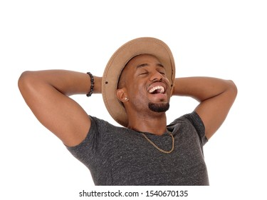 A closeup image of a very happy young African American man with his hands behind his head wearing a hat, isolated for white background