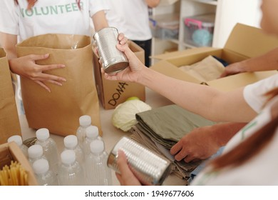Close-up image of volunteers packing canned food, bottled waterr and clothes in cardboard boxes to send it to hurricane victims