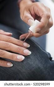Closeup image of a woman applying nail polish on her nail carefully