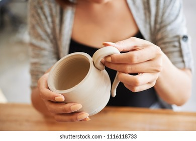 Close-up image of woman attaching handle to the mug she made