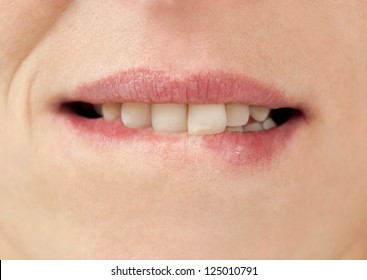 Close-up image of a woman bites her lips