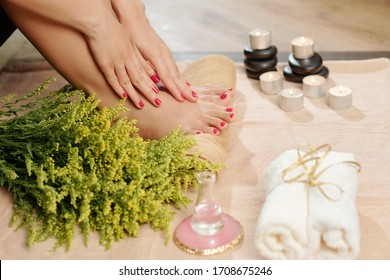 Close-up image of woman doing pedicure at home, she put burning candles around to create beautiful atmosphere