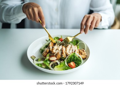 Closeup image of a woman eating chicken salad on table in the restaurant
