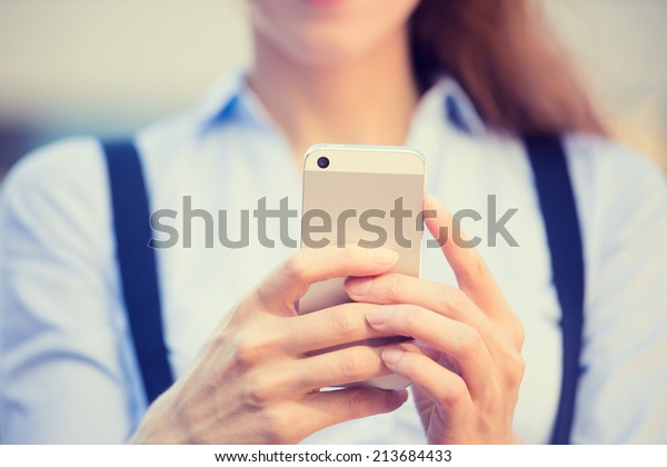 Closeup image woman hands holding, using smart, mobile phone isolated outside city background. New generation technologies, people phone addiction concept. Customer, service provider relationship
