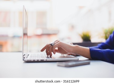 Close-up image of woman hands typing and writing massages on laptop,working on cafe.Overhead of essentials for modern young person.sensual woman reading and working,Urban