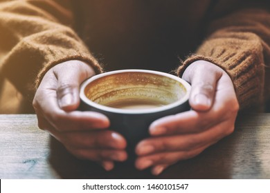 Closeup image of a woman holding a cup of hot coffee on wooden table