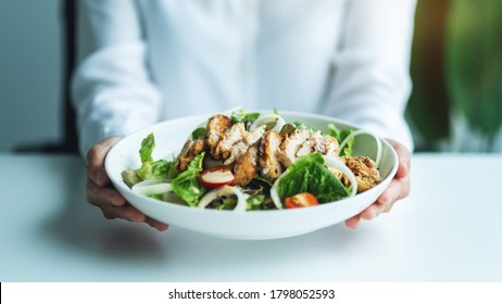 Closeup image of a woman holding a plate of chicken salad
