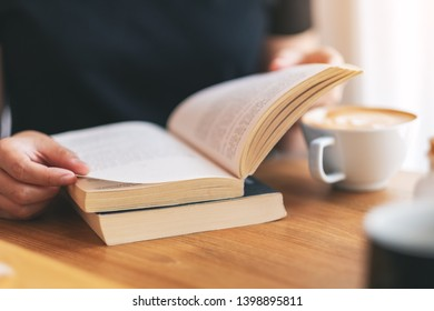 Closeup image of a woman holding and reading a vintage novel book with coffee cup on wooden table