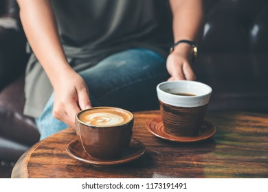 Closeup image of a woman holding and serving two coffee cup in the cafe