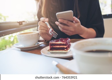Closeup image of a woman holding , using and looking at smart phone while eating a cake with white coffee cups and laptop on wooden table in vintage cafe