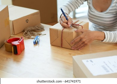 Close-up image of woman making note of giftbox
