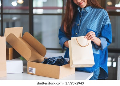 Closeup image of a woman opening and looking inside shopping bag with postal parcel box of clothing for delivery and online shopping concept