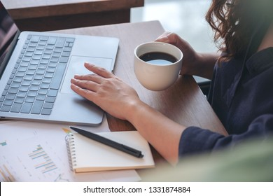 Closeup image of a woman touching on laptop touchpad while drinking coffee and working in office