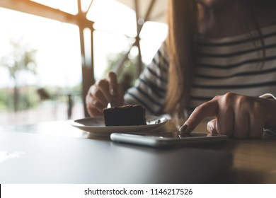 Closeup image of a woman using , touching and pointing atsmart phone while eating brownie cake in cafe